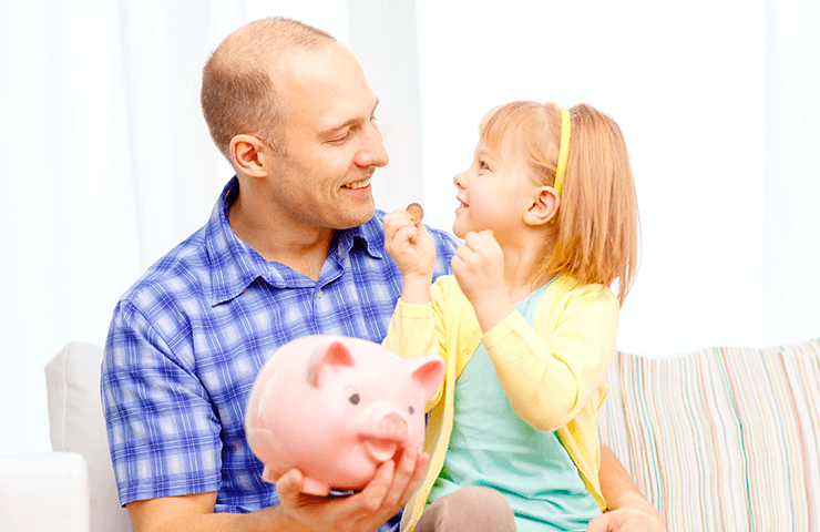 Father and young daughter with piggy bank
