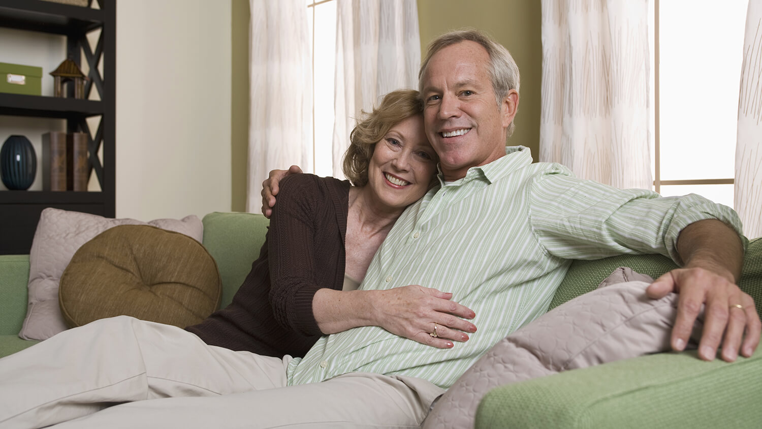 Happy middle-aged couple hugging on couch