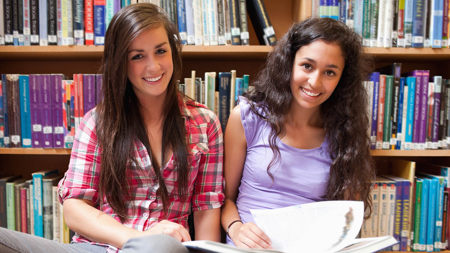 Two young women reading books in the library