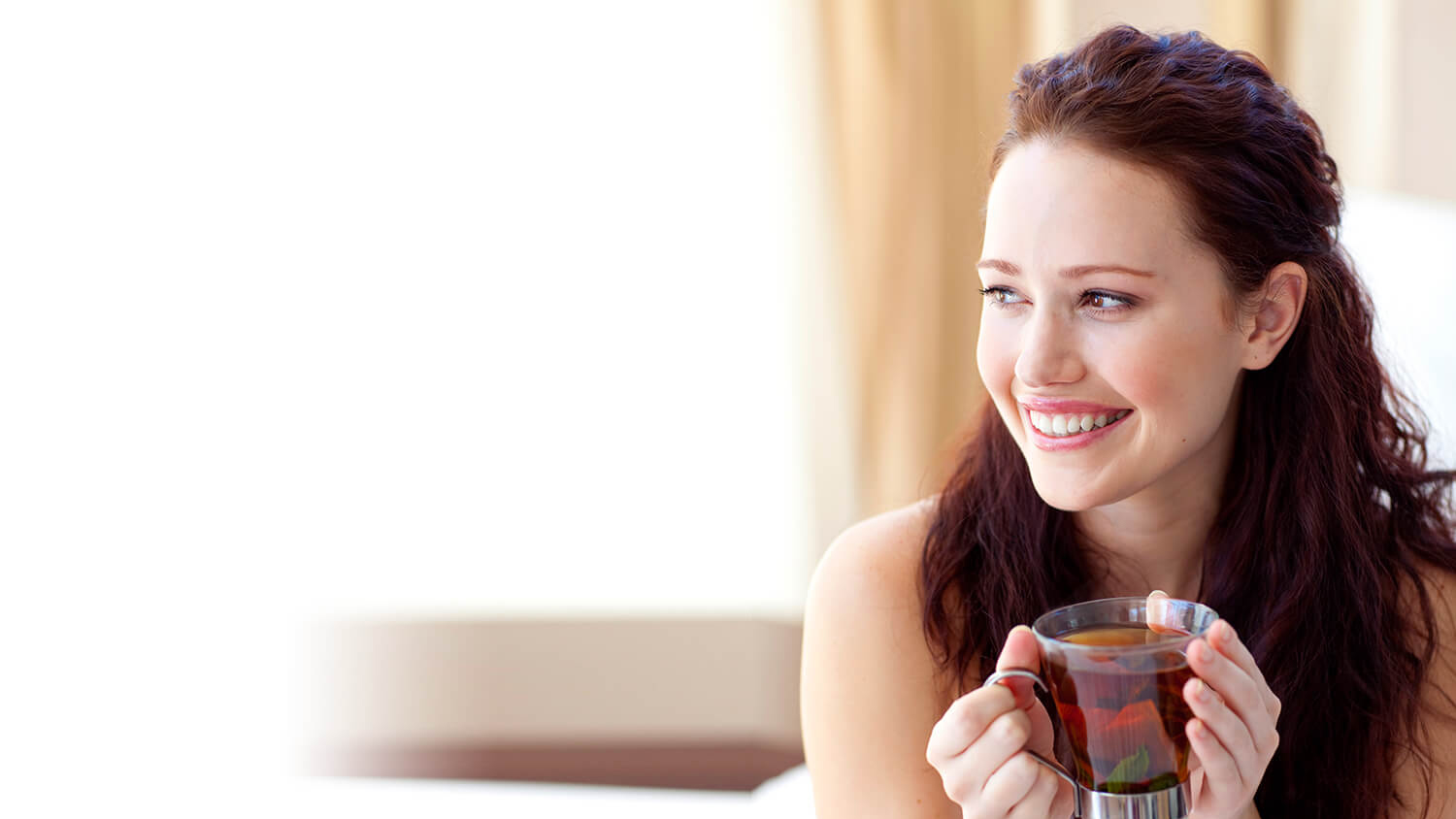 Young woman with coffee cup looking out a window