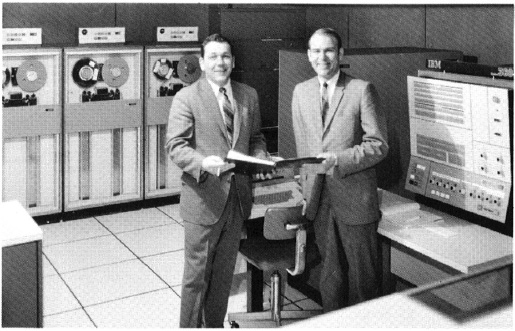 Illinois Mutual employees stand next to the Company's first mainframe computer.